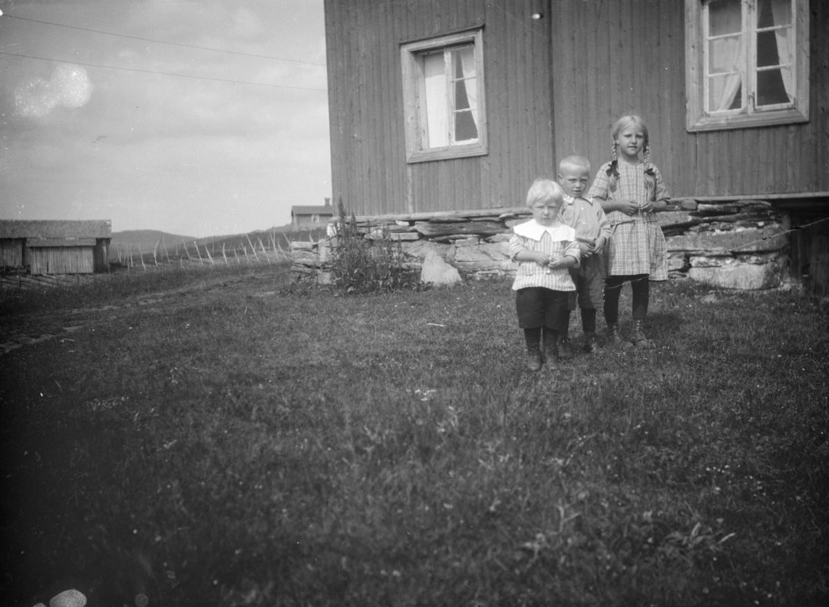 Tre barn foran et våningshus på ukjent gård