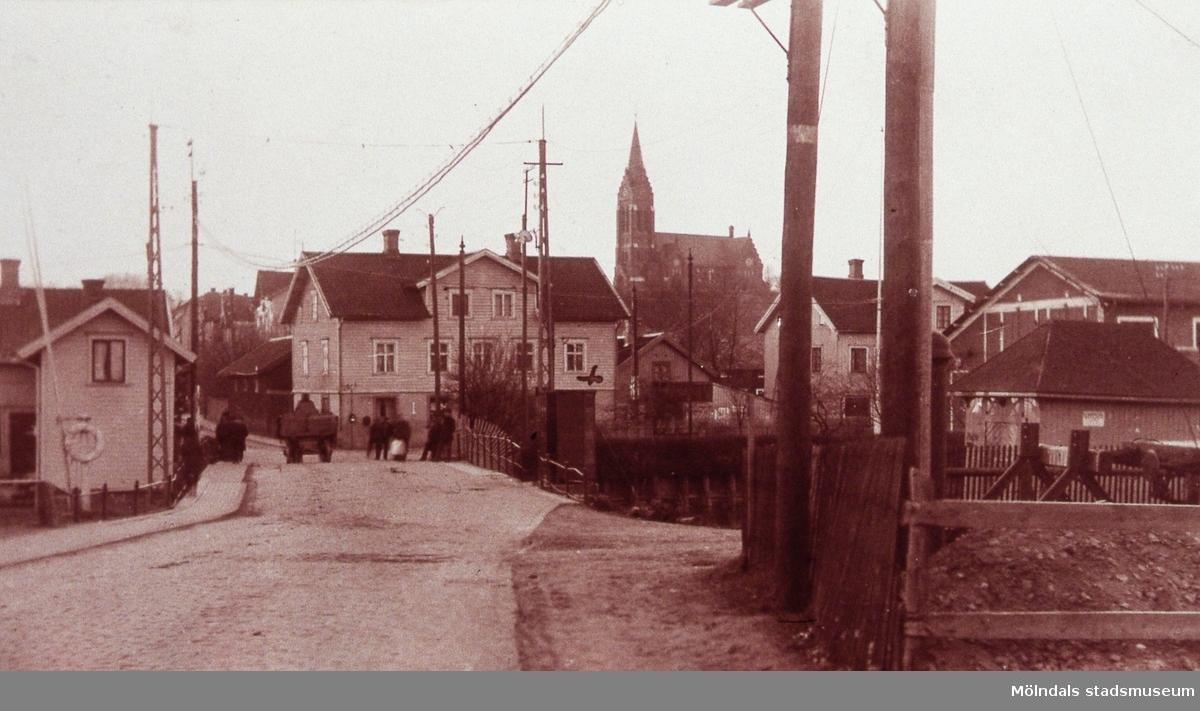 Avfotograferat vykort som skickats 1923. Mölndals Bro med järnvägsbommar. I bakgrunden ses Kungsbackavägen 1 samt Göteborgsvägen 1 och 3, spårvagnshallarna samt Fässbergs kyrka. AF 13:39.