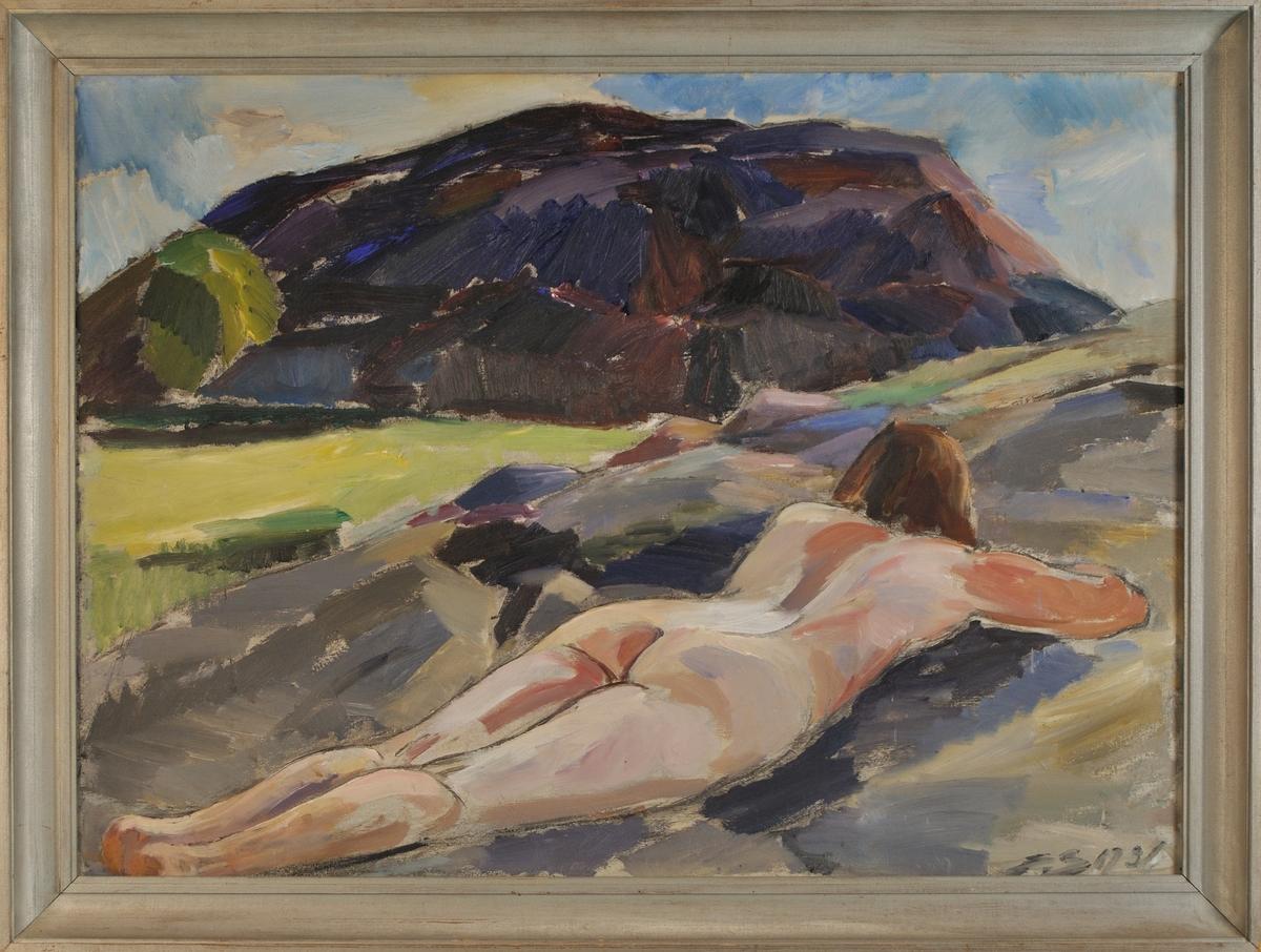 """Oljemålning. Naken flicka ligger i förgrunden, i bakgrunden ett berg i motsol. Motivet från Fiskebäckskil. Som modell har konstnärens hustru använts. Påskrift av konstnären a tergo: Evald Björnberg 1931 """"Västkustklippor""""."""