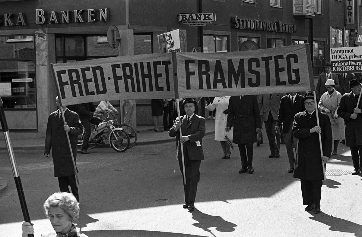 1:a majtåg, Demonstration på Nygatan. Demonstranter tågar med plakat. Skandinaviska Banken i bakgrunden.