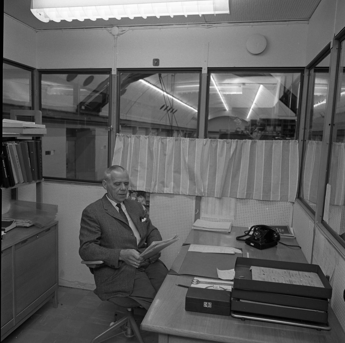 Alf Hedlund, maskinmästare, sitter på sitt kontor på Centrala Verkstaden Arboga. Han har en telefon på skrivbordet och en bokhylla bakom ryggen.