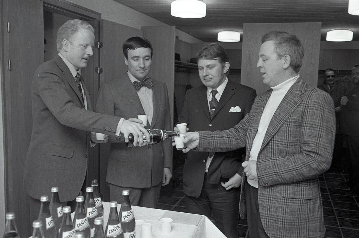 Arboga Bryggeri informerar. Fyra män är samlade i foajén, en trappa ner på biblioteket. De blir  serverade coca-cola ur en flaska. De räcker fram sina engångsplastmuggar. Två andra män skymtar i bakgrunden. Fantaflaskor står uppdukade på ett bord i förgrunden. Mannen med flugan är chefen för bryggeriet, Lars Andersson. Mannen med slipsen är chefen för EPA, Hans Lind. Längst till höger står styckmästare Lars Lindkvist som arbetar på ICA Asplund.  Anläggningen var färdigbyggd 1899 och verksamheten startade 1 november samma år. 24 oktober 1980 tappades det sista ölet, på bryggeriet. Märket var Dart. Läs om Arboga Bryggeri i hembygdsföreningen Arboga Minnes årsbok 1981