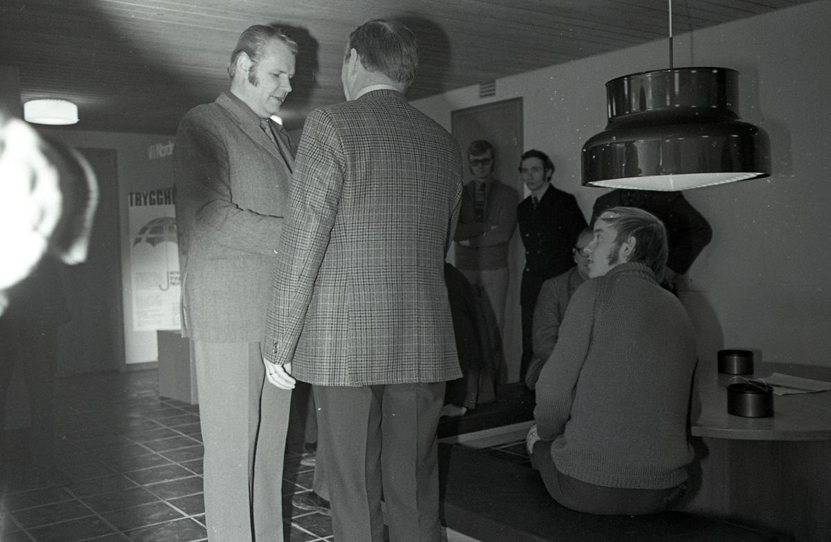 """Arboga Bryggeri informerar. Platsen är foajén, en trappa ner, på Stadsbiblioteket. (Den stora taklampan, över runda bordet, är IKEAs """"Bumling"""")  Endast en man är identifierad; Kaj Svensson, senare innehavare av Kajs Tobak på Nygatan. Han har mörk, dubbelknäppt kavaj och lutar sig mot väggen.  Anläggningen var färdigbyggd 1899 och verksamheten startade 1 november samma år. 24 oktober 1980 tappades det sista ölet, på bryggeriet. Märket var Dart. Läs om Arboga Bryggeri i hembygdsföreningen Arboga Minnes årsbok 1981"""