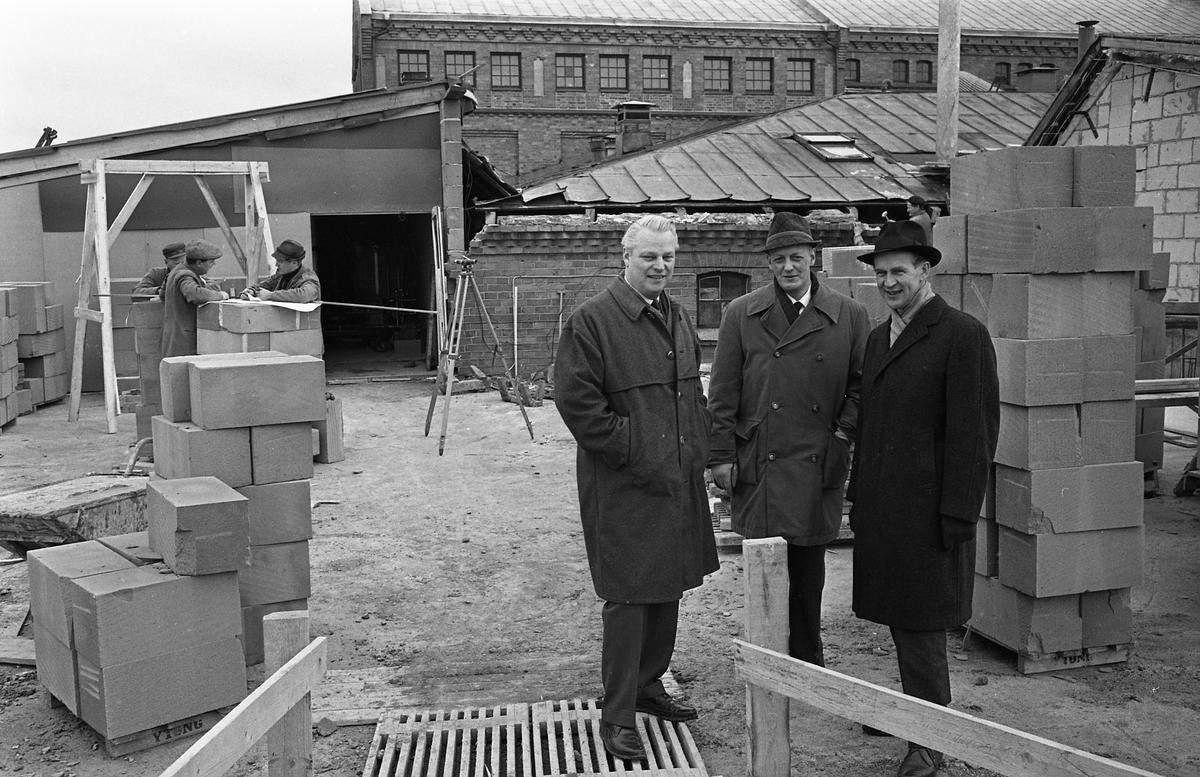 Arboga Bryggeri bygger egen bilverkstad med två portar. Tre män i ytterrockar står mitt i en byggarbetsplats. Bryggeriet syns i bakgrunden. Mannen längst till vänster är Karl Ivar Levert, bryggeriets chef. Intill honom står bryggmästare Ture Anderberg. Mannen längst till höger är okänd.  Anläggningen var färdigbyggd 1899 och verksamheten startade 1 november samma år. 24 oktober 1980 tappades det sista ölet, på bryggeriet. Märket var Dart. Läs om Arboga Bryggeri i hembygdsföreningen Arboga Minnes årsbok 1981