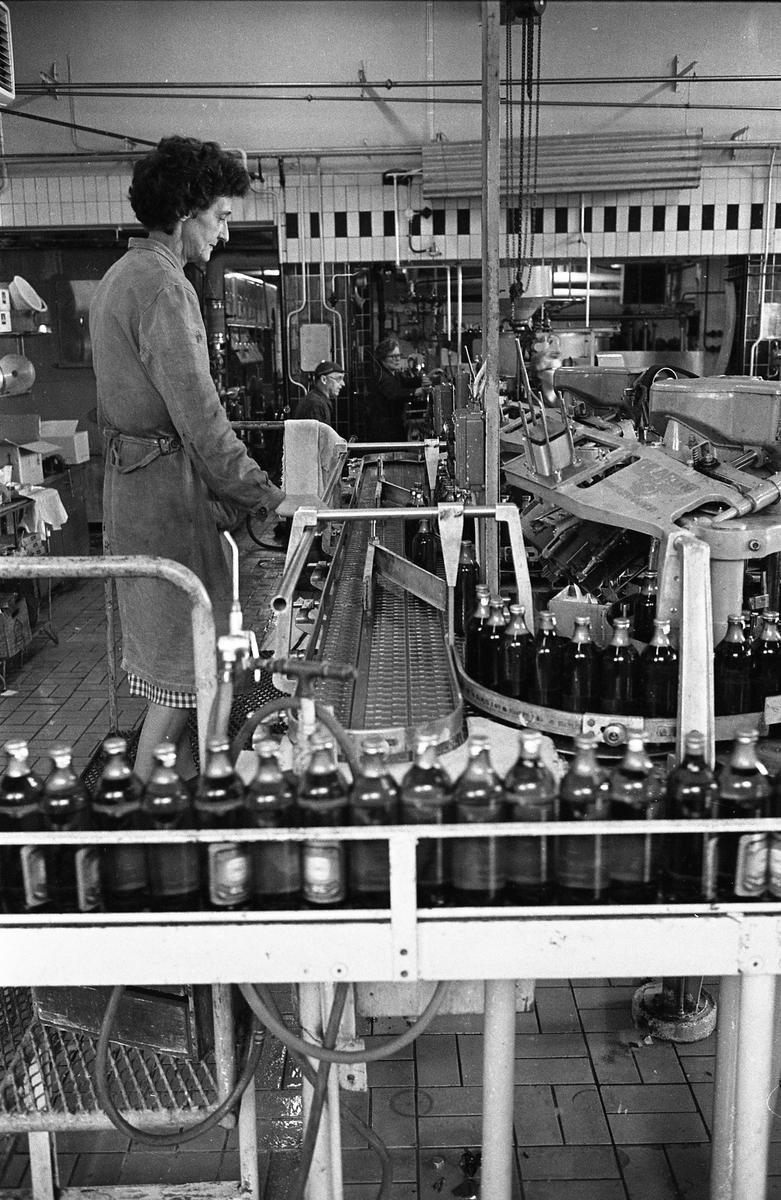 Arboga Bryggeri, interiör. Det är premiär för mellanölet. Fyllda ölflaskor transporteras på ett löpande band. En kvinna, iklädd arbetsrock, övervakar. Längre bak, i lokalen, jobbar en man och en kvinna med en maskin. Rummet har kaklade väggar och plattor på golvet. Kvinnan närmast kameran heter Britta Olsson.   Anläggningen var färdigbyggd 1899 och verksamheten startade 1 november samma år. 24 oktober 1980 tappades det sista ölet, på bryggeriet. Märket var Dart. Läs om Arboga Bryggeri i hembygdsföreningen Arboga Minnes årsbok 1981
