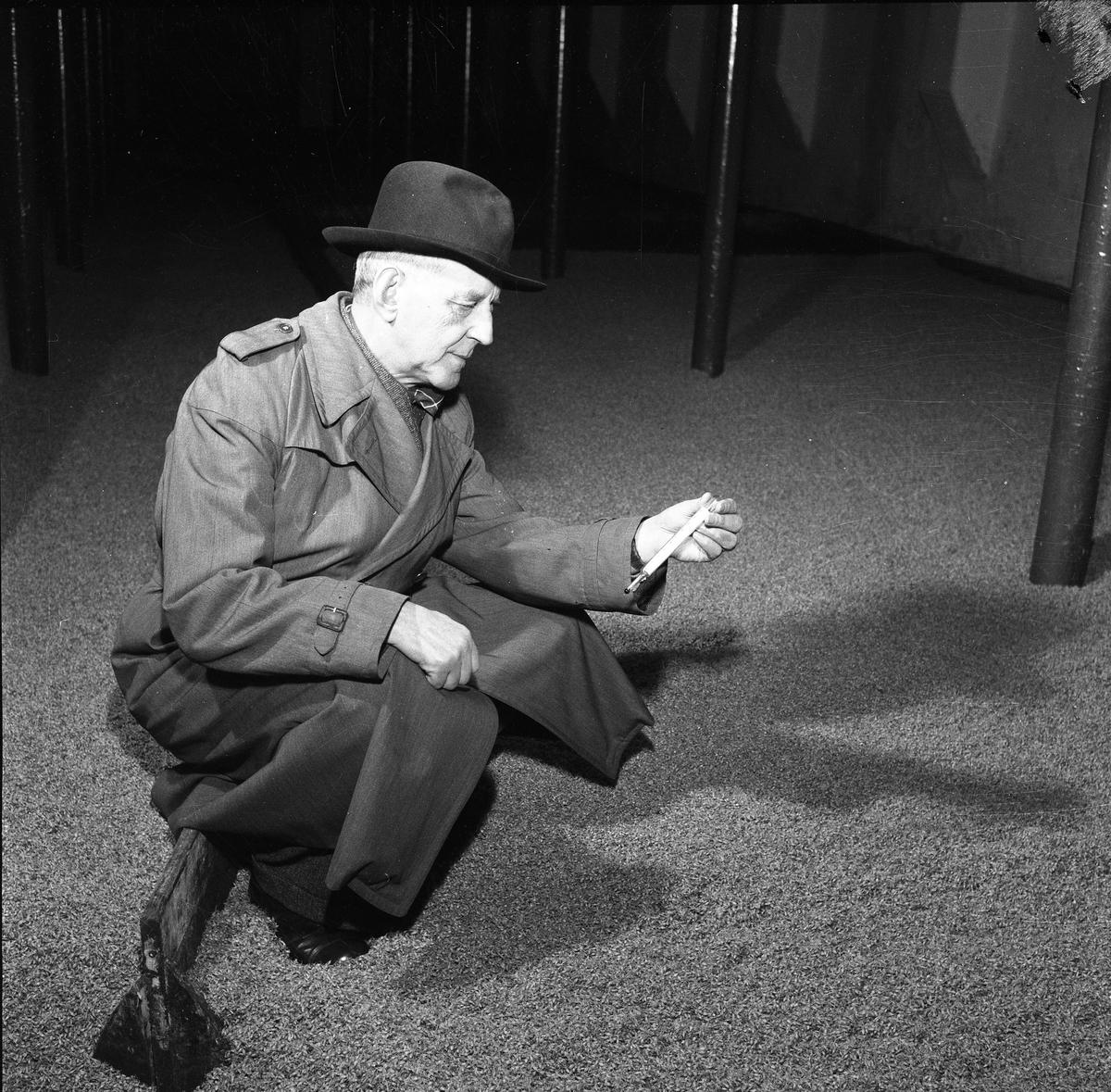 Arboga Kvarn och Maltfabrik, interiör. En man, iklädd överrock och hatt, sitter på huk vid mältan (=korn som legat i blöt i tre dygn och nu tappats ut på golvet). Han har en termometer i handen. Temperaturen är känslig; det ska helst vara mellan +8 - +10 grader. Blir det varmare kommer bladgrodden fram och så långt får inte groningsprocessen gå.  Mannen är disponent Carl Hugo Peterson. Han blev huvudägare 1935 och moderniserade både maltfabriken och kvarnen flera gånger.  Det som kom att bli Arboga Kvarn och Maltfabrik anlades 1821 av Jonas Örström. Kvarnrörelsen startade 1915. Vetemjöl av märket Guldsnö tillverkades här. Kvarnrörelsen upphörde 1967 medan maltproduktionen pågick fram till 1972.  Läs om Arboga Kvarn och Maltfabrik: Hembygdsföreningen Arboga Minnes årsböcker från 1979 och 1999 Reinhold Carlssons bok Arboga objektivt sett