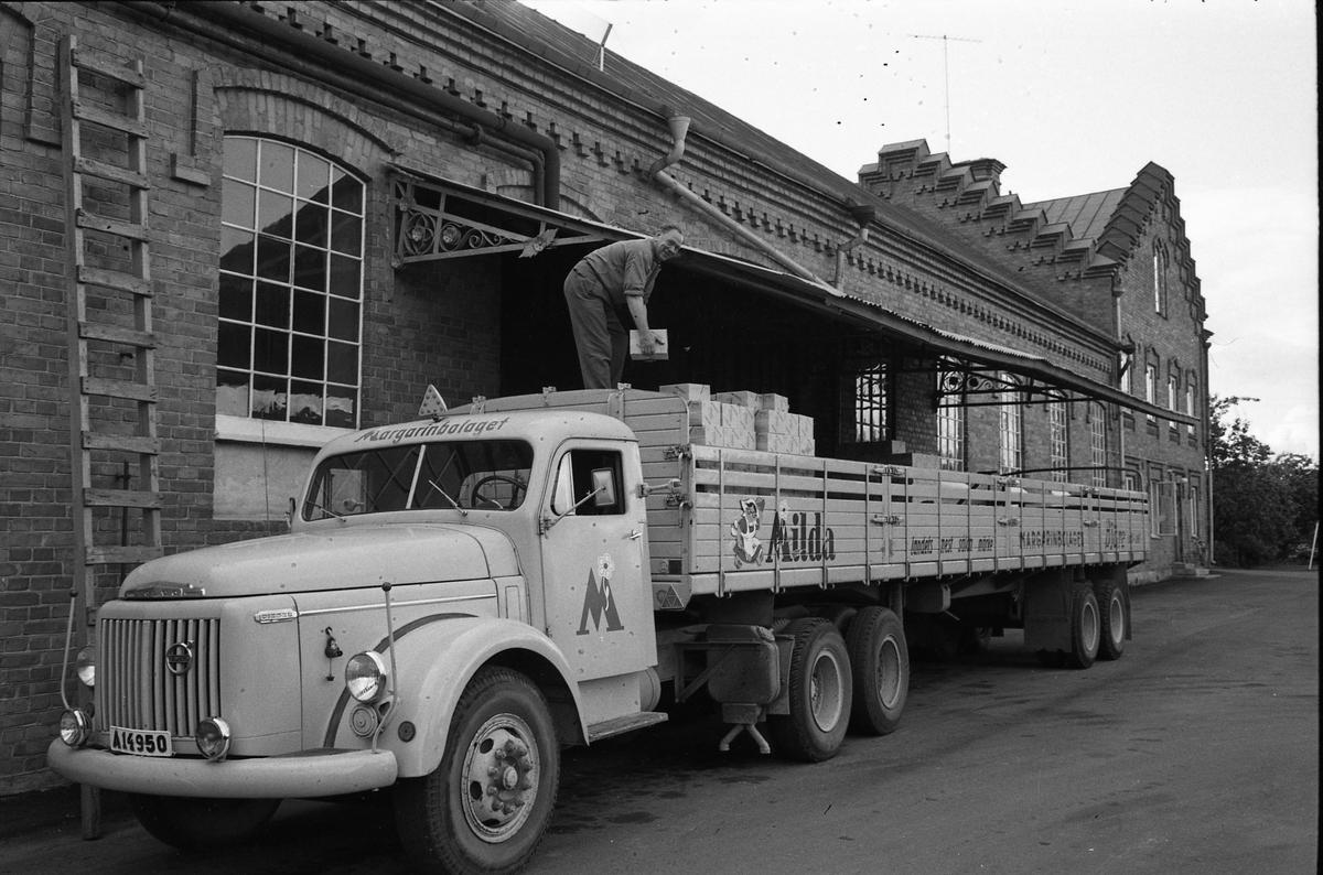 Arboga Margarinfabrik och en lastbil med texten Milda. På flaket är Holger Strömberg sysselsatt med att stapla margarinpaket. Detta är den sista utlastningen från Arboga Margarinfabrik. Trots att fabriken gick för fullt och nya paketeringsmaskiner just installerats, bestämde ledningen att fabriken måste läggas ner. Anledningen var att konkurrensen ökat och att fabrikens placering, inne i landet, gjorde det dyrt att frakta råvaror. Fabriken lades ner 30 september 1960. Läs om Arboga Margarinfabrik: Arboga Minnes årsbok 1978 Reinhold Carlssons bok Arboga objektivt sett