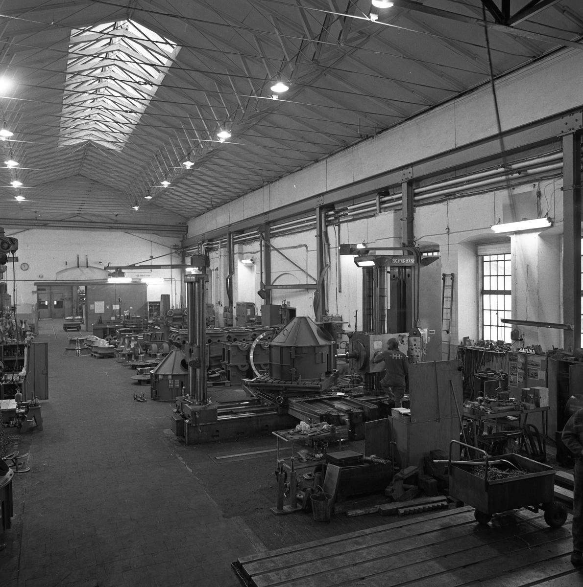 Arboga Mekaniska Verkstad, interiör från maskinverkstad och monteringsavdelning. Industrilokal med högt i tak och maskiner i dubbla rader.  25 september 1856 fick AB Arboga Mekaniska Verkstad rättigheter att anlägga järngjuteri och mekanisk verkstad. Verksamheten startade 1858. Meken var först i landet med att installera en elektrisk motor för drift av verktygsmaskiner vid en taktransmission (1887).  Gjuteriet lades ner 1967. Den mekaniska verkstaden lades ner på 1980-talet. Läs om Meken i Hembygdsföreningen Arboga Minnes årsbok från 1982.