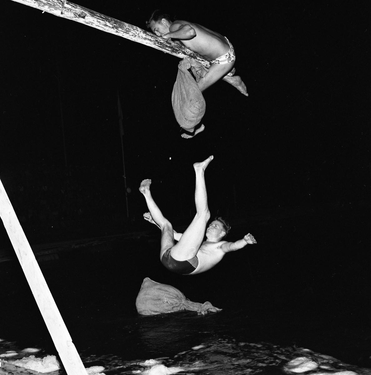 Arboga Simsällskap arrangerar Eldfest vid Villagatsbadet. Två män, iklädda badbyxor, har suttit på en bom / stång över vattnet. De har försökt slå ner varandra med var sin säck. Nu har en av dem vunnit, den andre faller mot vattnet. I mörkret, till vänster, anas publiken.