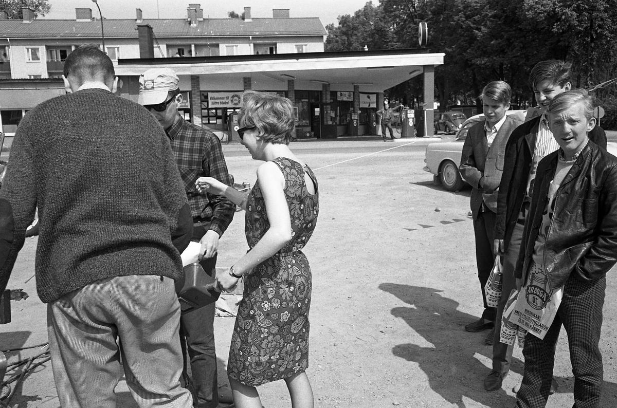 Arboga Tekniska skola. Äldre elever hittar på uppdrag till nykomlingarna. En kvinnlig elev, i blommig klänning, ska svetsa. En ung man är försedd med en skylt med Arboga Öls emblem. I bakgrunden ses Texacomacken med en man vid pumpen.