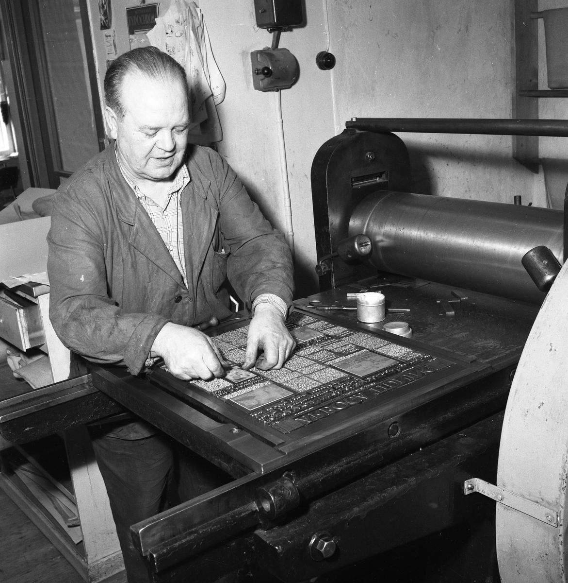 Arboga Tidning, personal och interiör. En man, iklädd skyddsrock, sätter en tidningssida. Han har trycksvärta på fingrarna. På väggen bakom honom finns en strömbrytare.