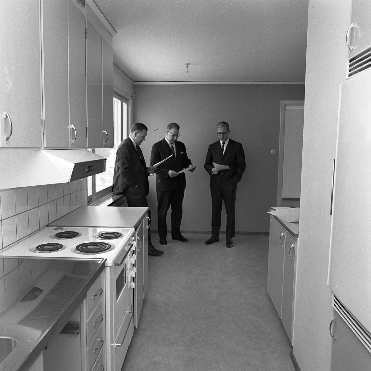 Arbogavillan lll, interiör, kök. Diskbänk, spis och köksfläkt i förgrunden. Tre kostymklädda herrar står i kökets matplats. I mitten står Hilding Lund på Byggnadsfirma Lund.