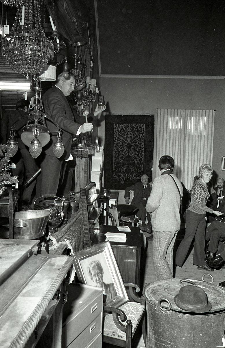 Auktion i Valskog. Auktionsförrättaren står på scenen med klubban i handen. I taket hänger kristallkronor och andra lampor. Byråar, kolkanna, kopparbalja, tavlor och mattor visas för försäljning.
