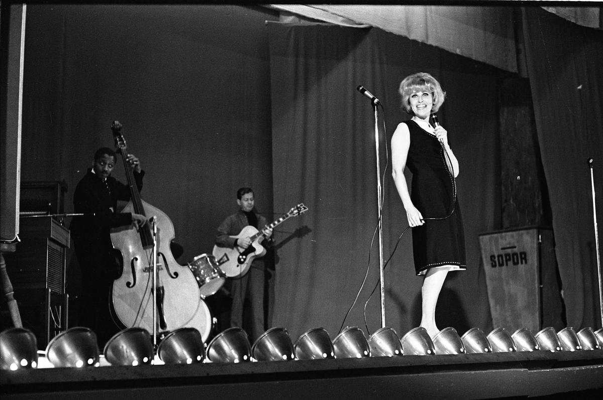 Sångerskan Bibi Johns uppträder på hemmaplan. Hon har musiker med sig på scenen; en man spelar kontrabas och en man spelar gitarr. Trummor ses i bakgrunden. Bilden är tagen i Folkets Park.