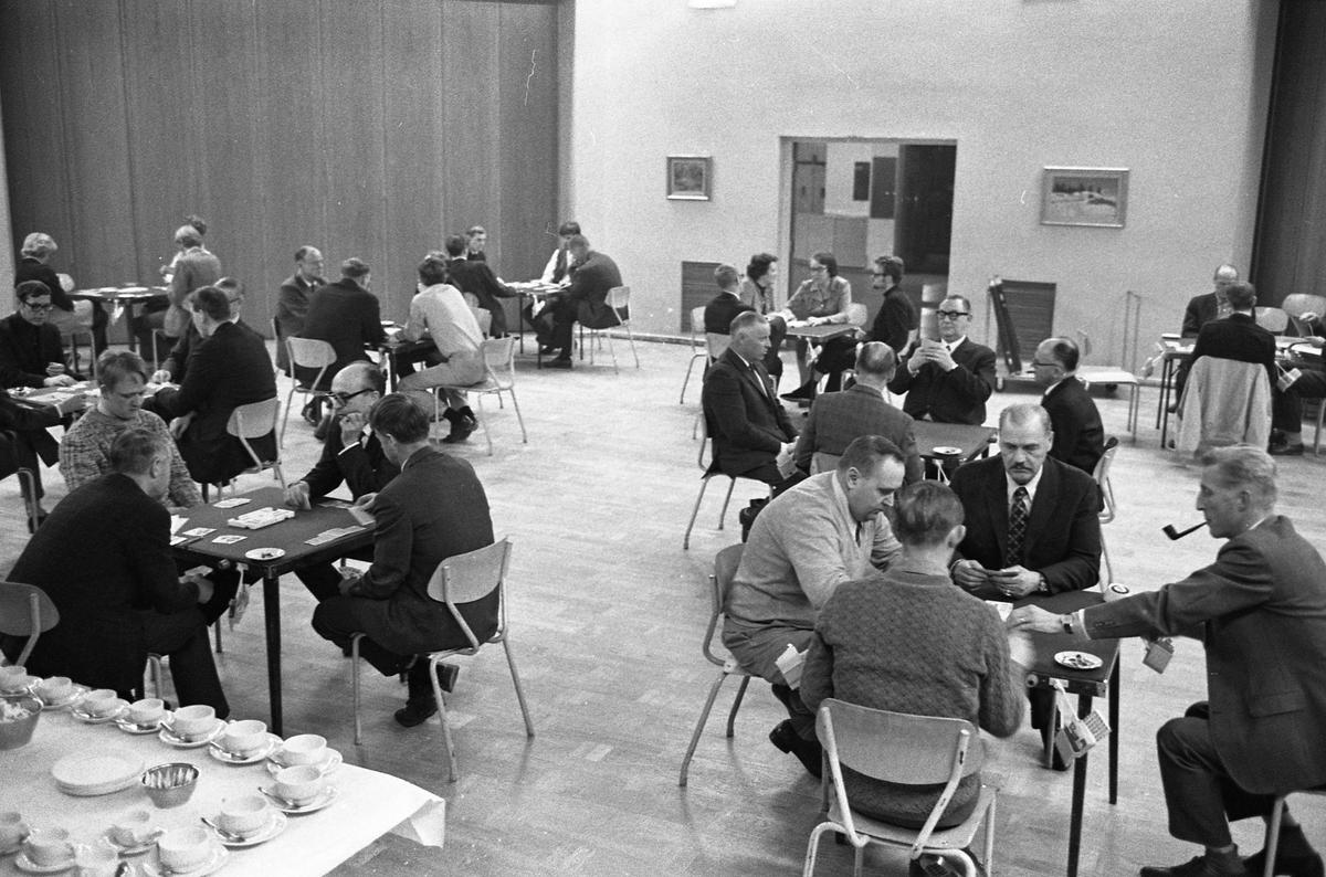 Bridge Människor sitter vid små bord och spelar kort. Platsen är Rotundan på Medborgarhuset. I förgrundan står ett bord dukat med kaffekoppar.