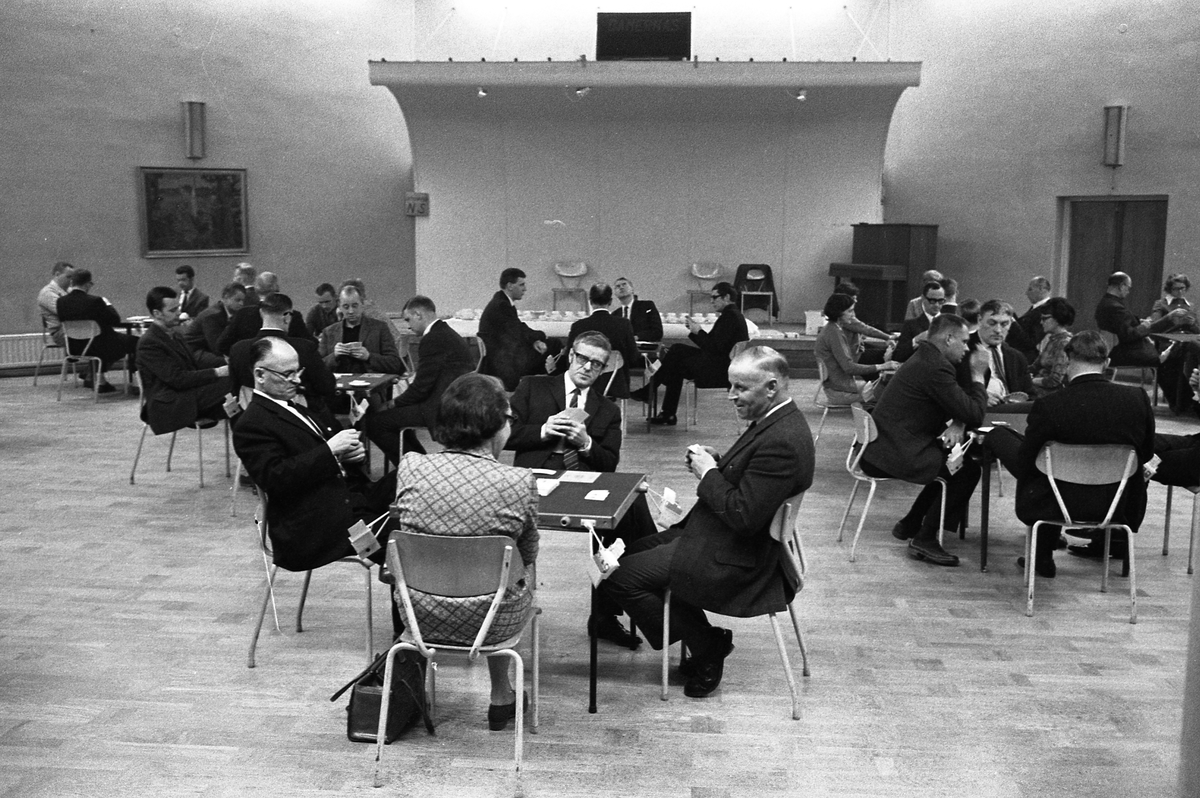Bridge i Medborgarhuset. Människor sitter vid bord och spelar kort. I bakgrunden ses scenen.