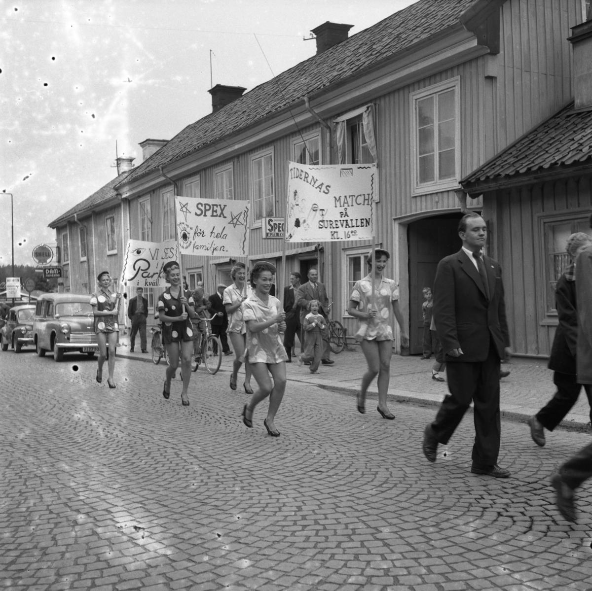 Casinorevyn i parad på Nygatan. Kvinnor bär skyltar om att det spelas fotbollsmatch på Sturevallen och att det blir ett nöje för hela familjen.