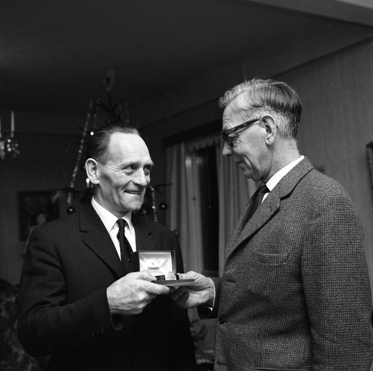 Einar Larsson i Hamre får en armbandsklocka. En man tar emot en gåva av en annan man. I bakgrunden ses en julgran.