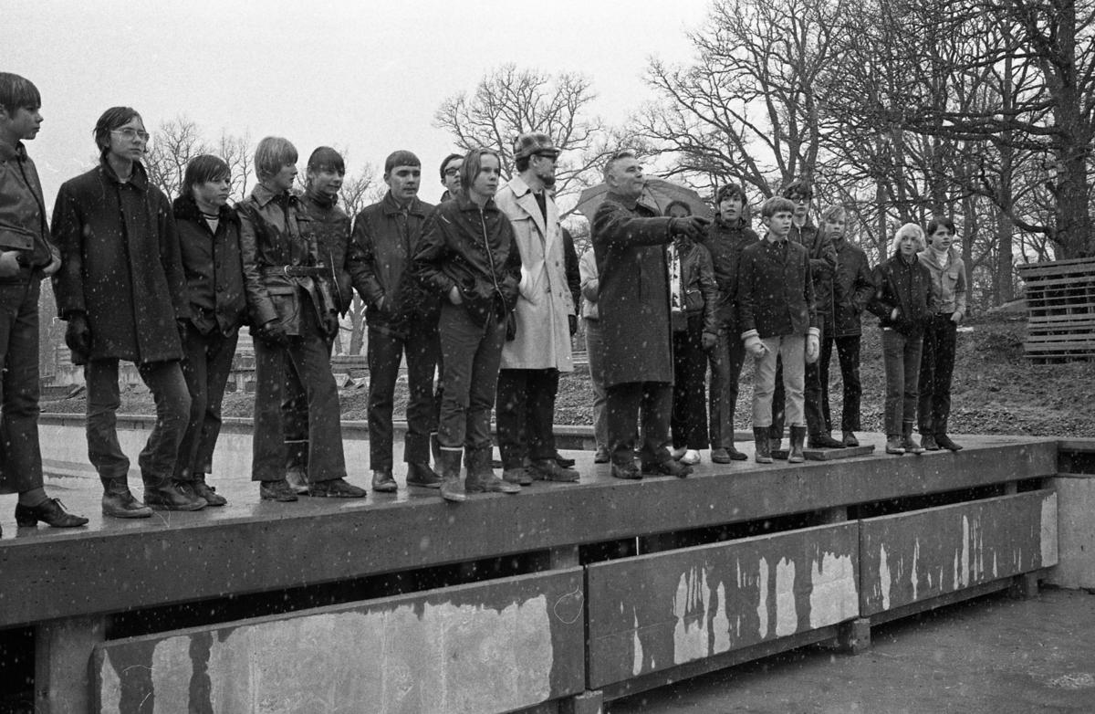 En skolklass är på besök på Ekbacksbadet, där utomhusbassänger ska anläggas. Nils Brodin pekar och berättar. Det är snöglopp. Några är iklädda gummistövlar. Ett paraply ses i bakgrunden. Några av grabbarna är identifierade, från vänster: okänd, Benny Karlsson, okänd, okänd, Leif Herling, okänd, Bo Wengelin står intill  läraren Sixten Öhman.  På höger sida om Nils Brodin står Per Andersson, Ulf Pettersson, thomas Schutz, Bengt Jansson, Pelle Olsson och okänd.