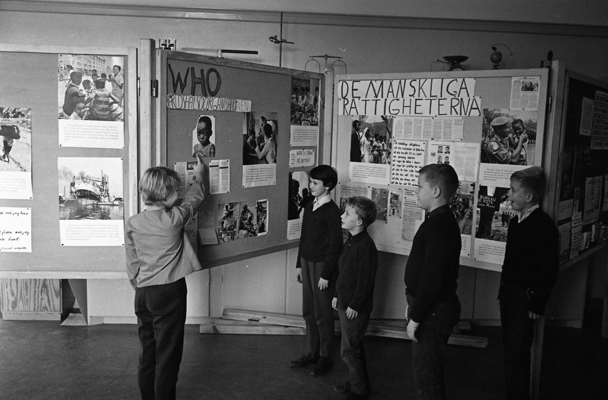 FN-dagen i skolan. Elever tittar på en utställning med bilder och texter om WHO och mänskliga rättigheter. Utställningen är uppsatt på vikskärmar.