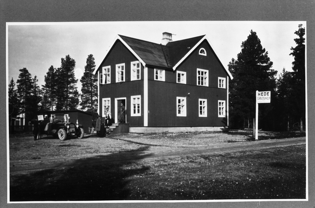 Avfotograferat foto Holms (oklart vad Reinhold menar med det) Hede Gästgiveri, står det på skylten. Män och kvinnor i trappan. Mannen i dörrhålen har eventuellt en chaufförsmössa på sig. På gårdsplanen står en öppen bil.