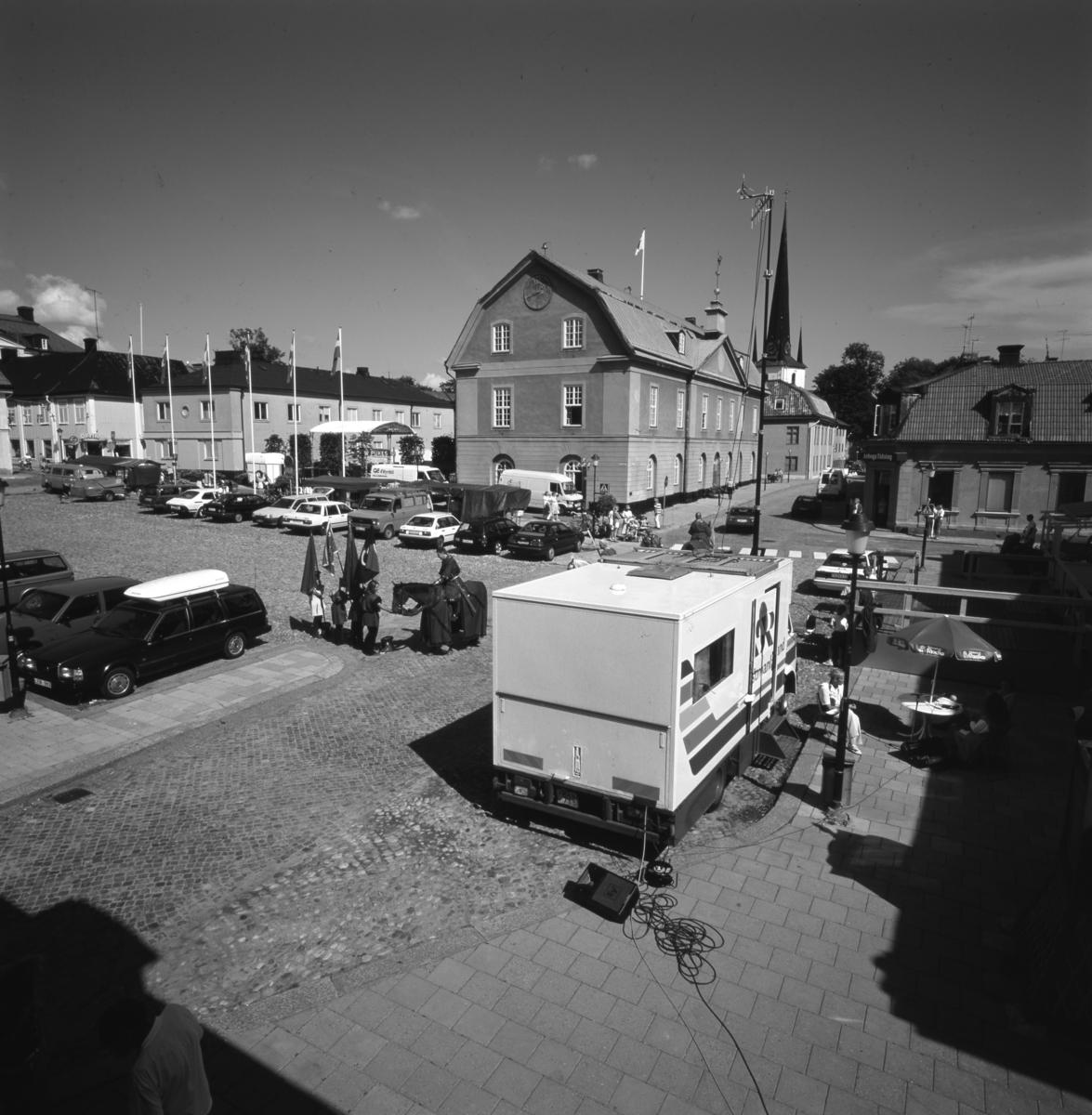 """Häst med riddarschabrak och riddare med fanor på Stora torget. Radio Västmanland har ställt upp sin sändningsbuss utanför Stadsgården. På trottoaren vid Rådhusgatan drar en ponny en vagn med två passagerare. """"Pukes"""" är möjligen en servering på Rådhusgården. Ett fönster är öppet i Kommunstyrelsesalen i Rådhuset. Bilar står parkerade i två rader på torget. I bakgrunden ses tornet på Heliga Trefaldighets kyrka. Medeltidsdagar? Fotografen har tagit bilden från ett fönster i sin bostad."""