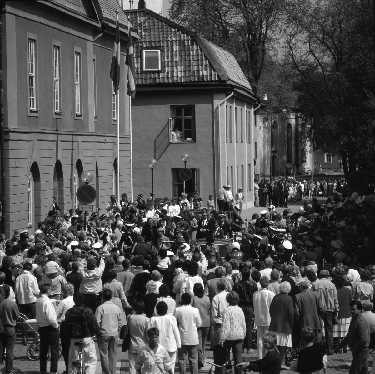 I Arboga firas 550-årsminnet av Sveriges första riksdag. Kungaparet, statsministern och ett stort antal riksdagspolitiker anländer till Arboga. Drottningen har klivit ur bilen på Rådhusgatan. Pressen är samlad. Poliser, till fots och på motorcykel, håller ordning på allmänheten. Medlemmar i Blåsorkestern, med sina instrument, ses till höger i folkhavet. Någon tittar ut genom ett fönster på Musicum. Heliga Trefaldighetskyrkan anas i bakgrunden. Riksdagsjubileet 1985
