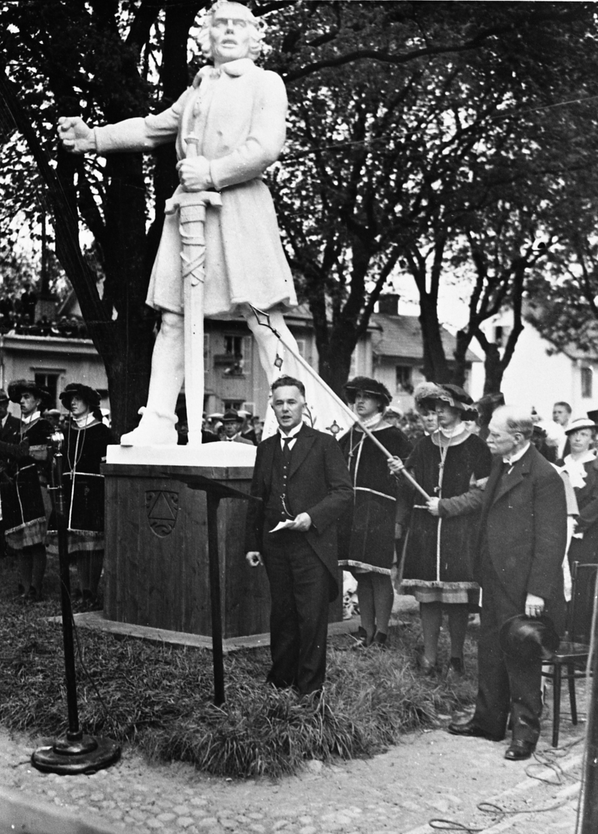 Riksdagsjubileet 1935 500-årsminnet av Sveriges första riksdag. En man håller tal nedanför statyn av Engelbrekt (som är av gips). Bakom honom står några medeltidsklädda män och publiken. Repro för jubileumsalbum