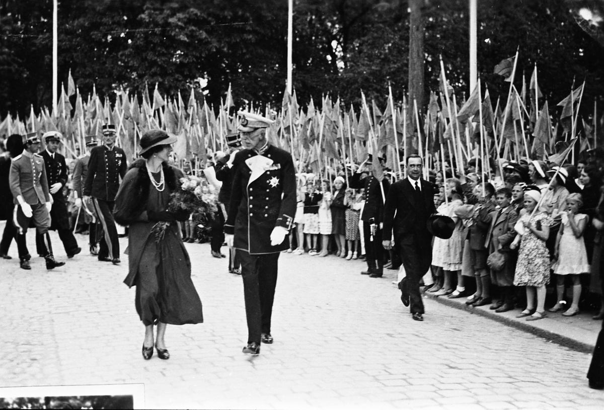 Riksdagsjubileet 1935 500-årsminnet av Sveriges första riksdag. Kronprinsessan Louise och kung Gustaf V följda av uniformsklädda medlemmar ur hovet. Till höger går borgmästare Wilhelm Wester. Skolbarn med flaggor kantar vägen. Repro för jubileumskatalog