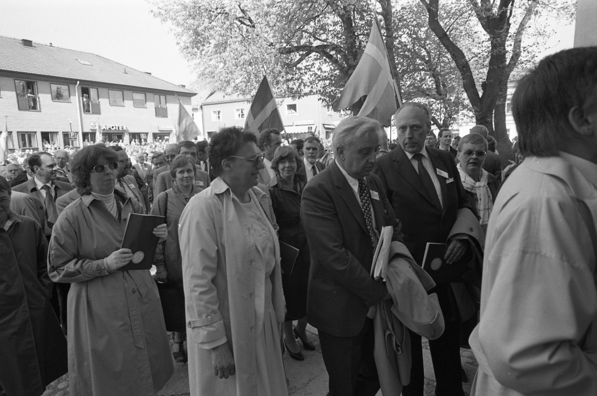 Riksdagsjubileet. I Arboga firas 550-årsminnet av Sveriges första riksdag. Politiker, så väl lokala som på riksplanet, är på väg in i Heliga Trefaldighetskyrkan. I bakgrunden ses Apoteket och Bellis Blommor. Allmänheten hålls på behörigt avstånd, på andra sidan Järntorget. Flaggorna vajar.