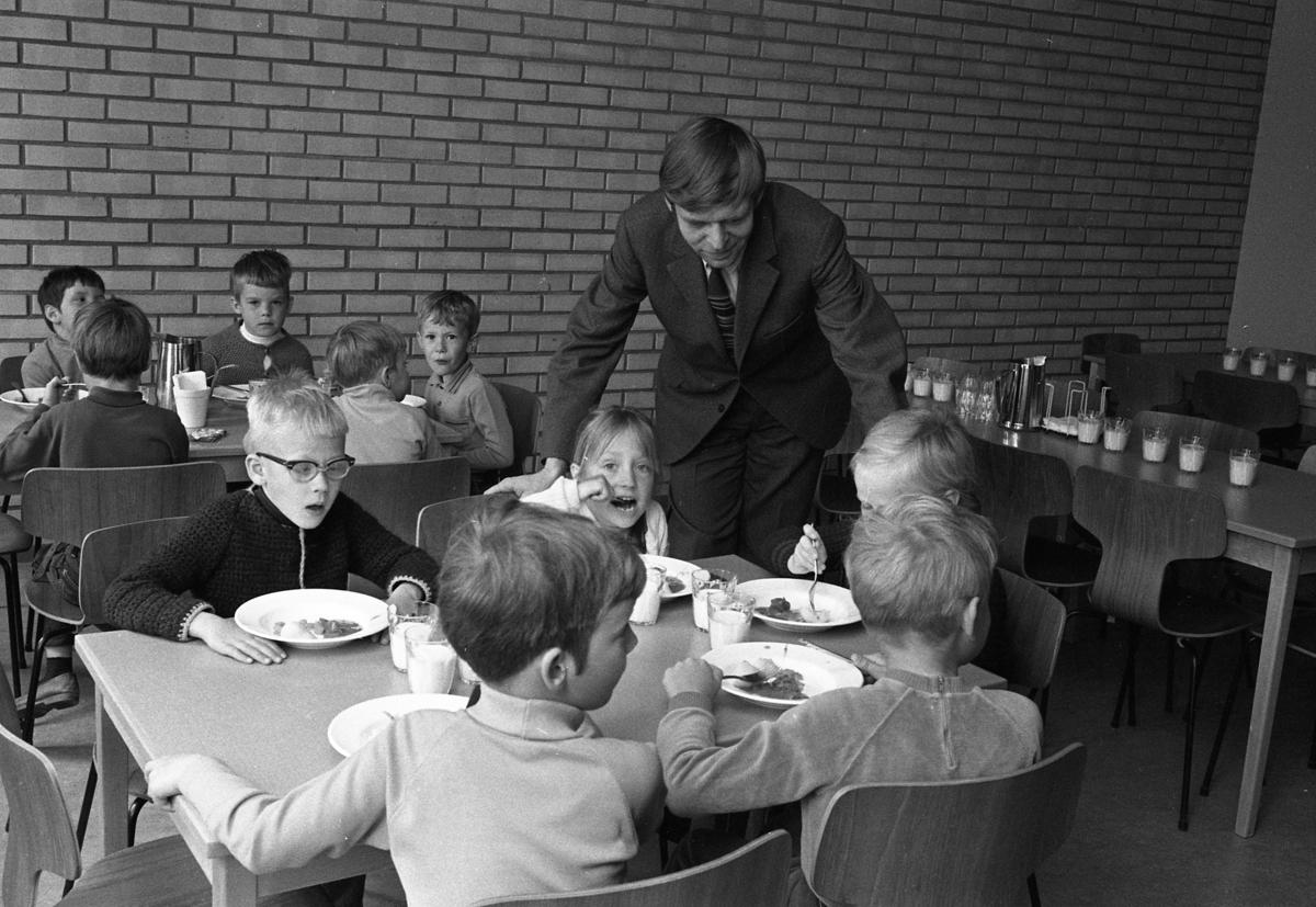 Skolchef Per Thorstensson visar skolan för barn från lekskolan. Ett besök i skolbespisningen ingår. Barn som sitter och äter vid två bord. De har mjölk i glasen.