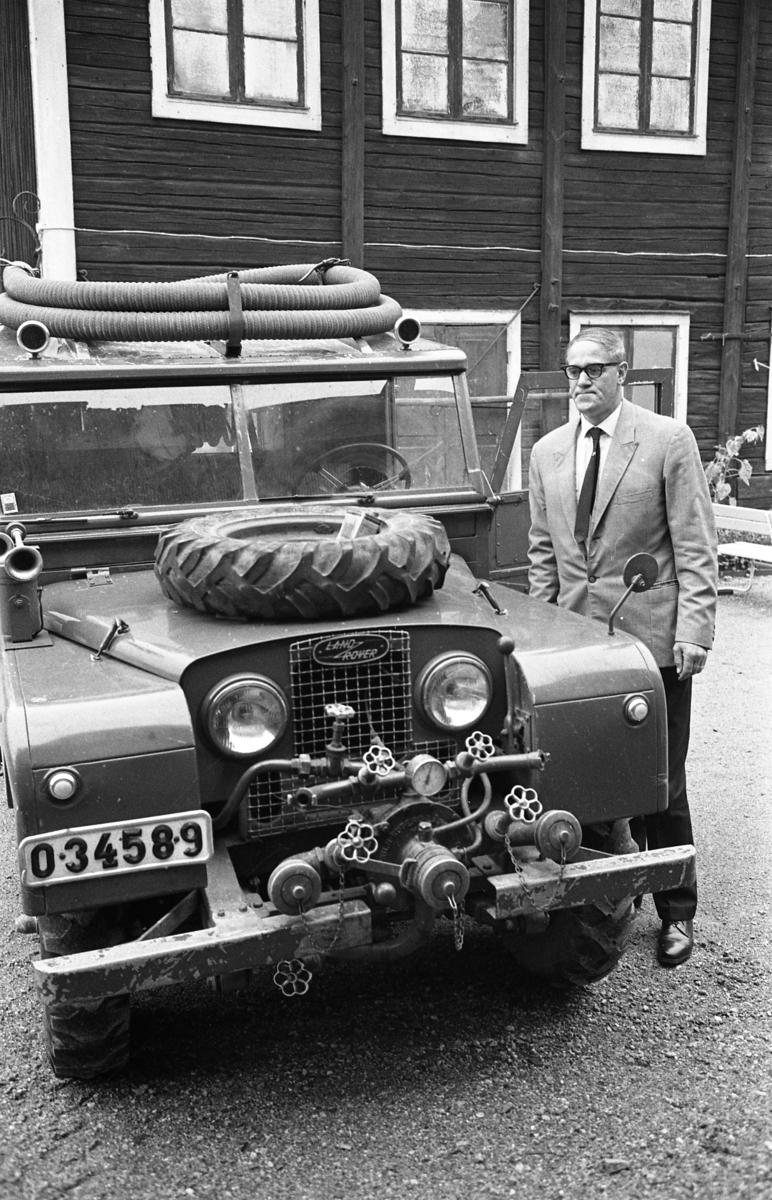 Polisman Sigurd Granberg inspekterar en stulen brandbil. I bakgrunden ses ett flervånings trähus.