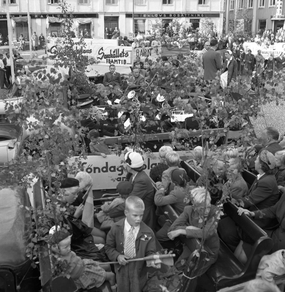 Söndagsskolans Dag firas. Flera lastbilar, med lövade flak, står uppställda på Stora torget. På flaken sitter barn men två lastbilar transporterar var sin blåsorkester. I bakgrunden ses butikerna Haglund och Eklöws Bosättning.