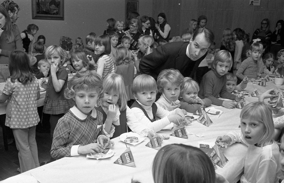 Söndagsskolan har julfest. Barnen bjuds på Festis och bulle. Tre långbord är dukade. Det är många barn på festen, några vuxna deltar också. Prästen heter Rolf Larsson. De tre barnen närmast honom är syskonen Rosén; Johan Rosén, Anette Rosén och lillebror Paul Rosén (med bullen i munnen).
