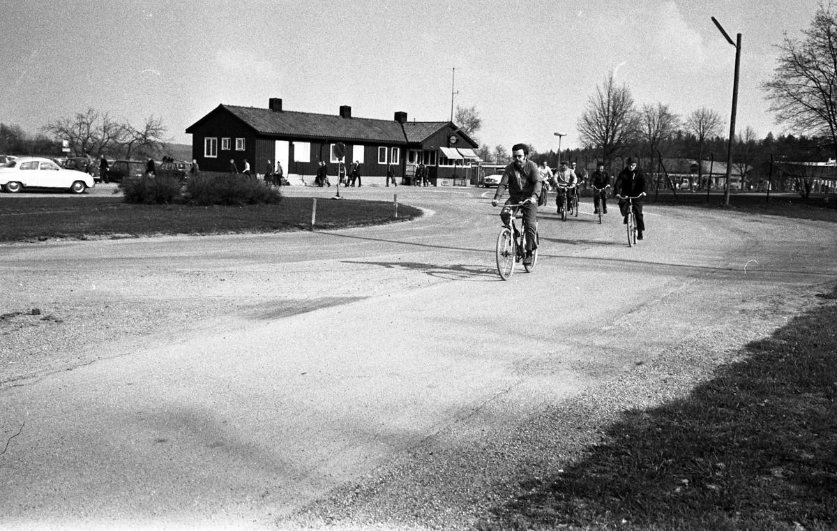Arbetsdagen är slut. Män cyklar hem från CVA, Centrala Verkstaden Arboga. I bakgrunden ses bilparkeringen, byggnaden där vakten sitter och en SAAB som är på väg ut genom grinden.