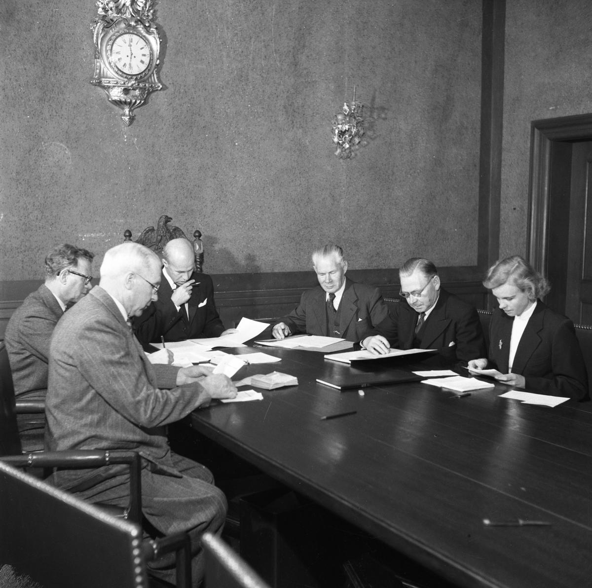 Valnämnden sammanträder i drätselkammarsalen på Rådhuset. Från vänster: Vidar Adolfsson, Georg Linell, borgmästare Daniel Ekelund (ordförande), Emanuel Carlsson, Erik Ring och Mary Zilo (kommunaltjänsteman) På väggen hänger en pendyl.