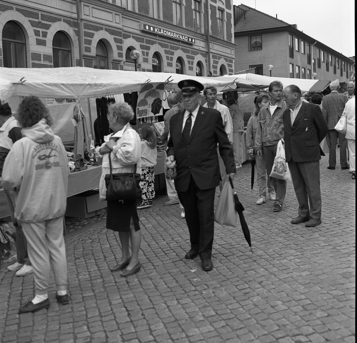 """Höstmarknad. Människor i alla åldrar strosar bland torgstånden. Där erbjuds bland annat paraplyer. En man i Frälsningsarméns uniform promenerar med en insamlingsbössa i ena handen. Paret bakom honom, klädda i jeansjackor, är Annika Sörén och Lars Sörén. I bakgrunden ses """"Gamla Sparbankshuset"""" med klädbutiken """"TeHås"""" i hörnet Järntorget - Rådhusgatan."""