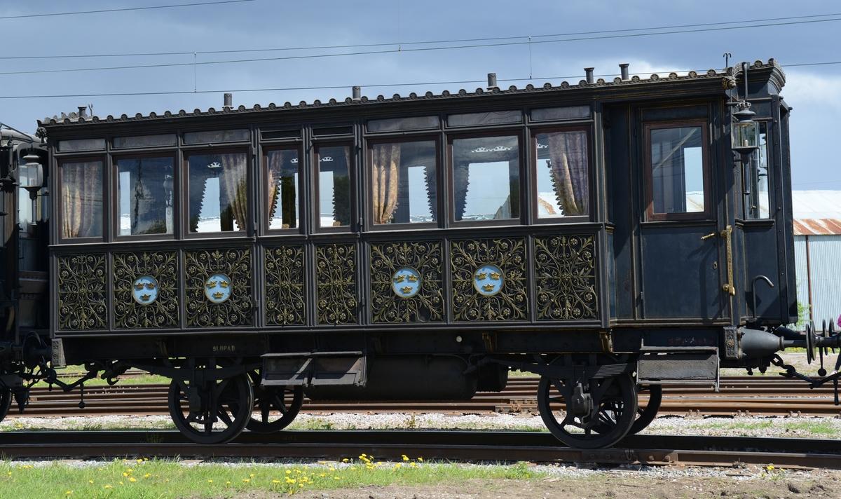 """Nr 4, Oscar II:s audiensvagn. Audiensvagn som använts av Oscar II. Vagnen är mörkblå med sirliga järndekorationer efter sidorna, blomrankor målade i guldfärg med runda fält med """"Tre kronor"""" mot blå botten. Fönsterna på vagnens ena kortsida, samt i ena änden av salongen har etsade dekorationer. Även över fönsterna på vagnens långsidor finns ett fält av etsat dekorerat glas. Upptill kröns vagnens tak av en list med fleur de lys, samt lejon genom vilkas gap regnvatten från taket kan rinna ut. Vagnen har fyra lyktor utanpå, en i varje hörn, och den är märkt upptill i varje ände med de latinska siffrorna IV. Den har handtag, dörrvred och kasthakar av brännförgylld brons. Vagnen är indelad i ett förrum och en salong.  Salongen har invändigt ett baldakinliknande tygklätt tak i guldrödrandigt fint ylletyg, och tre infällda gaslampor i taket. Golvet täcks av brunröd linoleumsmatta med blågula geometriska stjärnmönster. Vagnen har 6 stora fönster längs med varje långsida, samt även en dubbeldörr med fönster mitt på varje långsida. Tunga golvlånga draperier eller gardiner av rödbrunt blommönstrat ylletyg hänger vid alla fönster. Samtliga draperier har tofsar längs med hela kanten. Alla fönster i salongen har fönsterremmar av mönstervävt siden med lilla riksvapnet på guldbrun botten, remmarna är avslutade med platta tofsar.  I ena änden har vagnen en mininal vestibul eller ett förrum med väggar klädda med gyllenläderimitation, tak klätt med grått ripstyg, samt fällbara väggfasta säten med rottingsits. Alla fönster i vestibulen har rullgardiner av gråbeige siden, vissa är trasiga. Fönsterremmarna i förrummet har mönster av lilla riksvapnet på vit botten, med platta tofsar i ändarna. Från vestibulen leder dubbeldörrar in till salongen. Dörrarna har dörrspeglar av valnöt, samt på insidan spegelglas med stora riksvapnet i guld.  Inventarier: 4 rödklädda träsoffor av valnöt med snidade karmar och ryggstöd. Sofforna har rottingsitsar med lösa sittdynor, medan ryggdynorna är fästa med"""