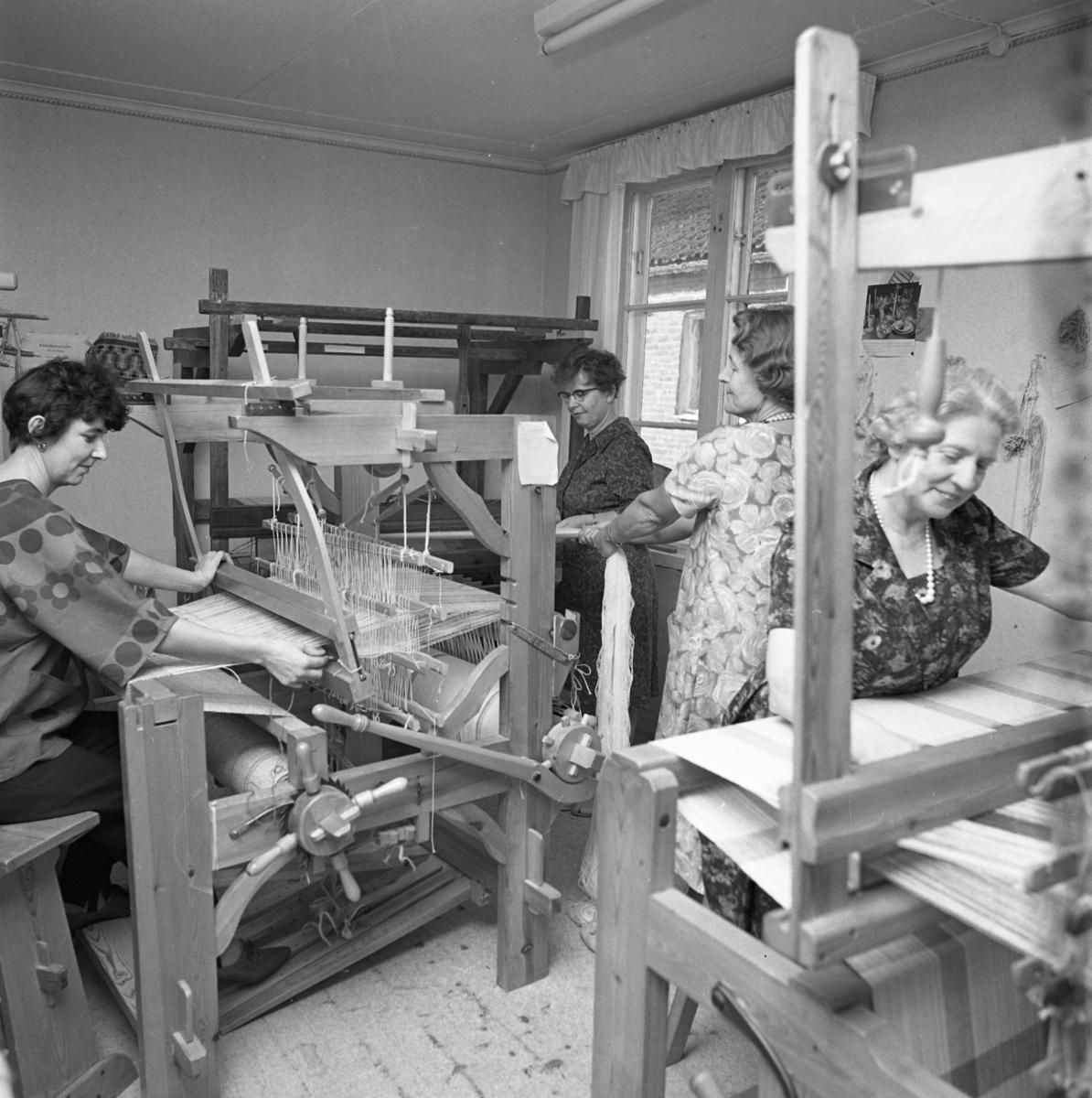 Husmodersföreningens vävstuga. Två kvinnor väver och två kvinnor hjälps åt att dra på en väv.