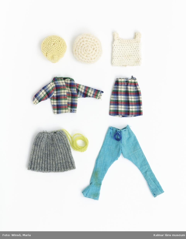 KLM45643:25 Dockkläder. Hemsydda kläder. Virkad skärmmössa i gult garn. Virkad basker i vitt syntetgarn. Vitt virkat linne. Jacka och kjol i rutigt tyg – rött, grönt blått, vitt och svart. Kragen kastad med grönt garn. Tryckknappar. Stickad mudd som omvandlats till kjol. Stickad i grått garn med varannan maska rät och varannan avig. Grönt garn för att knyta i midjan. Turkosvita byxor med blå tråd för att knyta i midjan. Linne i randigt tyg – vitt, lila, blått, grönt, rosa. Hals och ärmhål kastade med lila garn. Sjalett av blå-vit-rött tyg. Vikt dubbel och hopsydd med ljusblått garn. Huvudbonad av vinrött tyg. BH av rosa tyg och gummiband. Samtliga dessa plagg är tillverkade av givarens mamma Inga-Greta Nilsson för Barbie. Byxor med utsvängda ben och vad som ska vara en väst. Båda i blått tyg med turkosa och gröna blommor. Tillverkade av Ann-Sofie för Barbie.