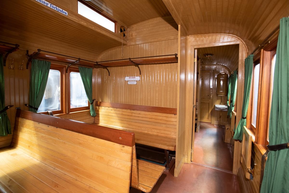 Kombinerad personvagn för första/andra och tredje klass (första och andra klass fr.o.m. 1956), SJ BCo1 nr 1032. 1893 års modell. Boggivagn. Andraklassdelen är grönmålad utvändigt och  tredjeklassdelen brun. I övrigt gula inramningar och gul text. Taket är svart med lanternin. Andraklassdelen (18 sittplatser) med brunklädda bäddbara soffor, samt bruna gardiner. Blommigt toalettporslin. Tredjeklassdelen (44 sittplatser) är inredd med ribbade träbänkar och gröna gardiner.