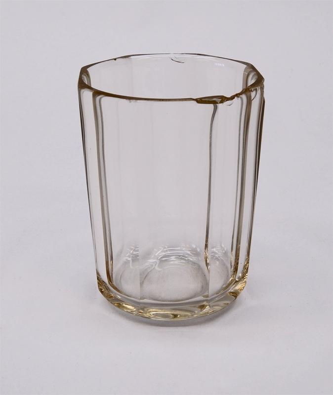 Dricksglas av genomskinligt glas. Det är åttkantigt och rundas av längst ned vid botten.