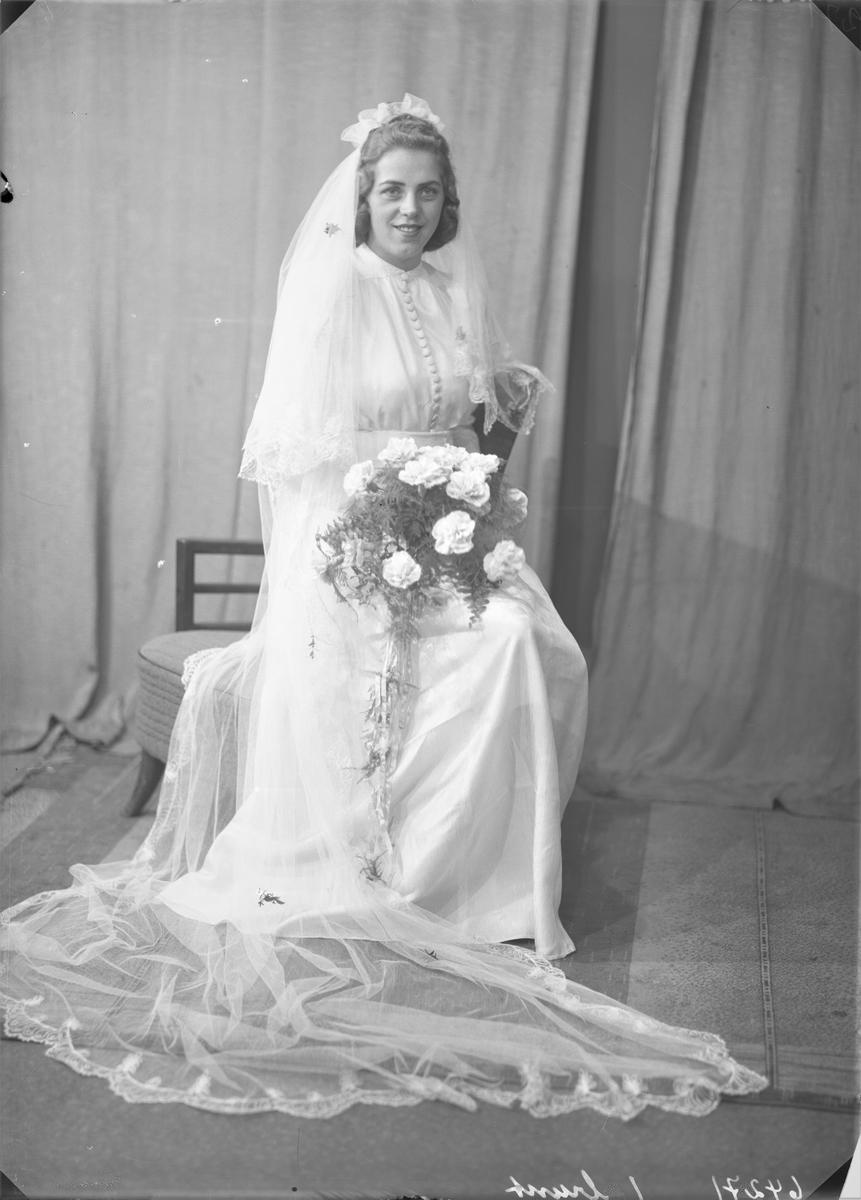 Portrett. Brudebilde. Ung lyshåret kvinne med lang hvit brudekjole med slør og blomsterbukett. Brud. Bestilt av John Pedersen.
