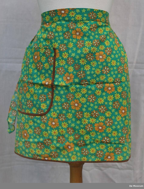 Forkle med lomme på høgre side og knyteband rundt livet. Det er kanting langs forklet og lomma. Mønsteret i stoffet viser forkjellige blomar.