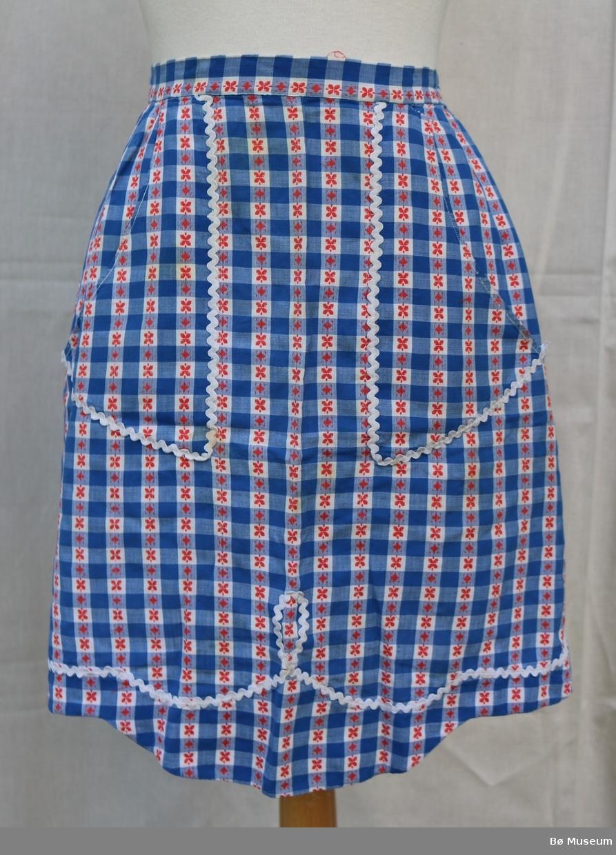 Forkle i blått, ljoseblått og kvitt rutemønster, og raude blomar.  Det er ei lomme på kvar side. Over sømmen på to sider av lommene har kvit, bølgete kant. Denne kvite, bølgete kanten går også i ei stripe i botnen av forkle.