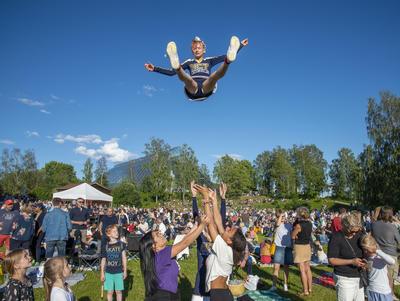 Cheerleaderjente blir kastet høyt opp i lufta.