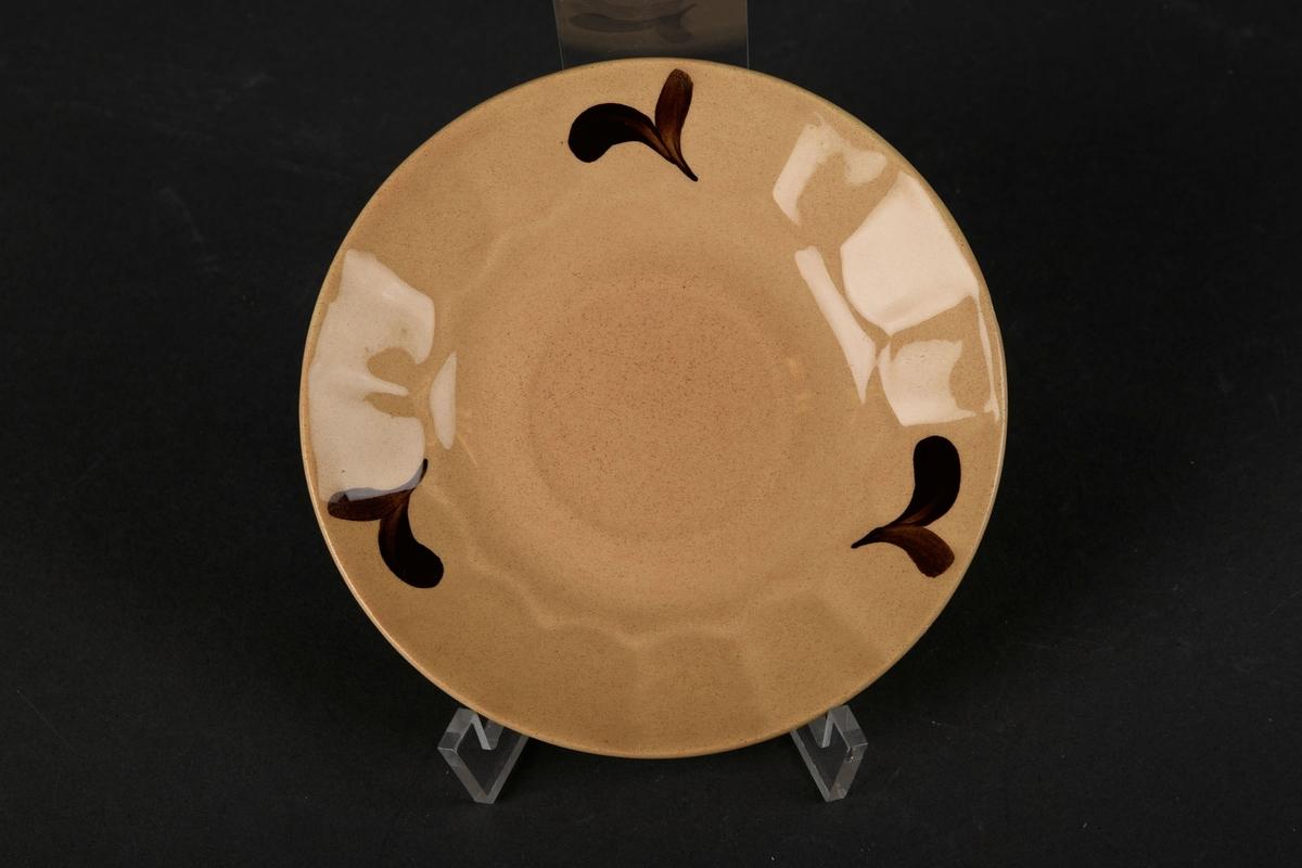 Besj tefat med brun dekorasjon.