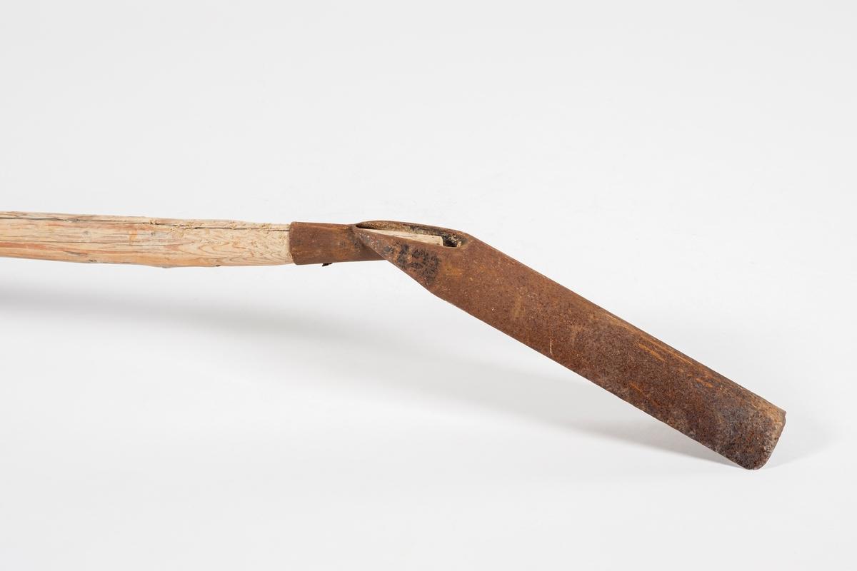 Langt treskaft med et slags graveresdskap i jern på. Jernet ser ut som et halvt rør og står i en skrå vinkel nedover i forhold til skaftet.