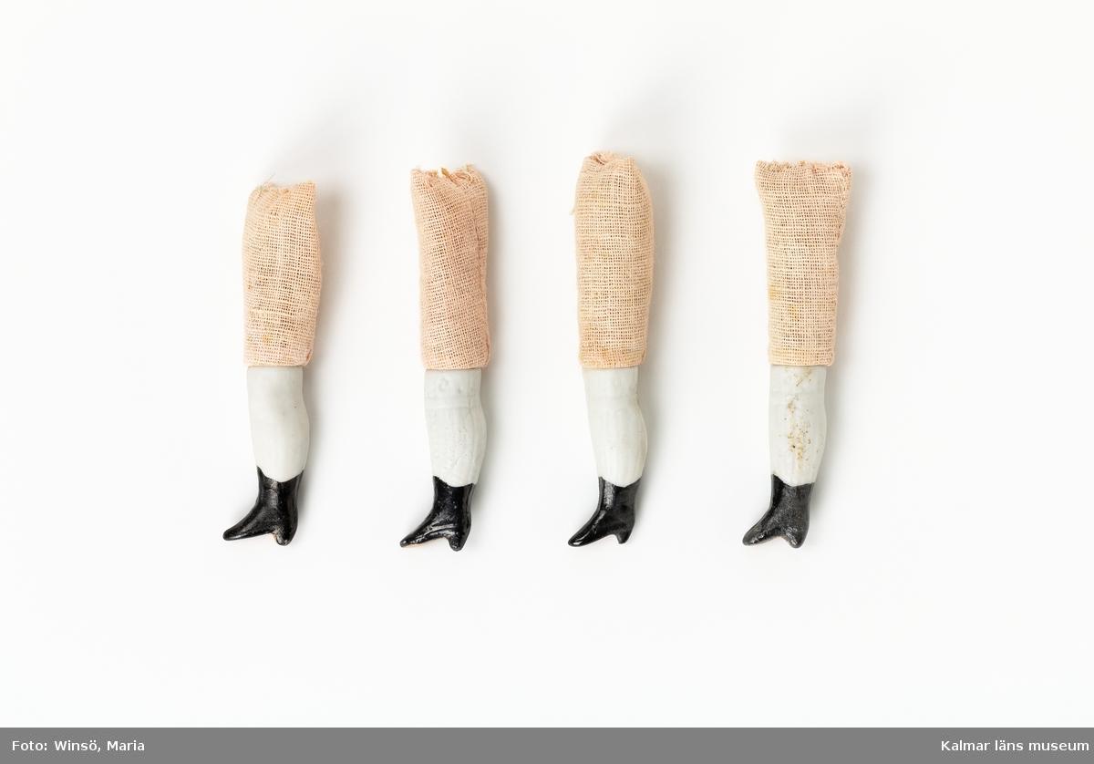 KLM 28082:206 Dockben, 4 stycken, av porslin, bomull och spån. Upp till knä, ben av porslin, högskaftad sko med klack, svartmålad, vad och knä, vitmålad. Lår, sydd av aprikosfärgad bomullsväv och fylld med stoppning av spån.