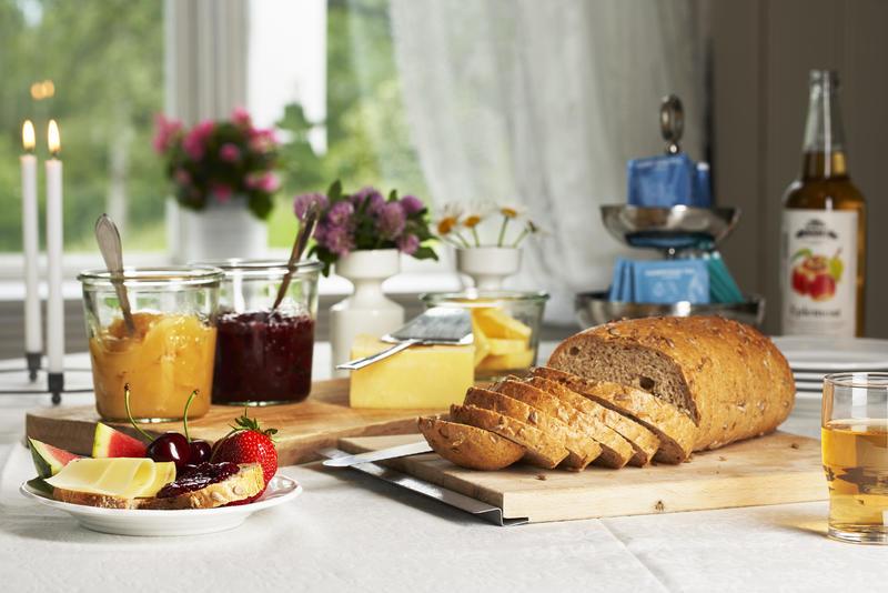 Et pent dekket frokostbord med brød, eplemost, syltetøy og ost. Blomster og levende lys i bakgrunnen